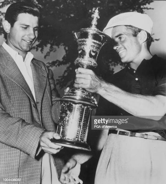 Finalists in the USGA National Amateur tourney Sam Urzetta of Rochester NY and Frank Stranahan of Toledo OH look over the cup that one will win...