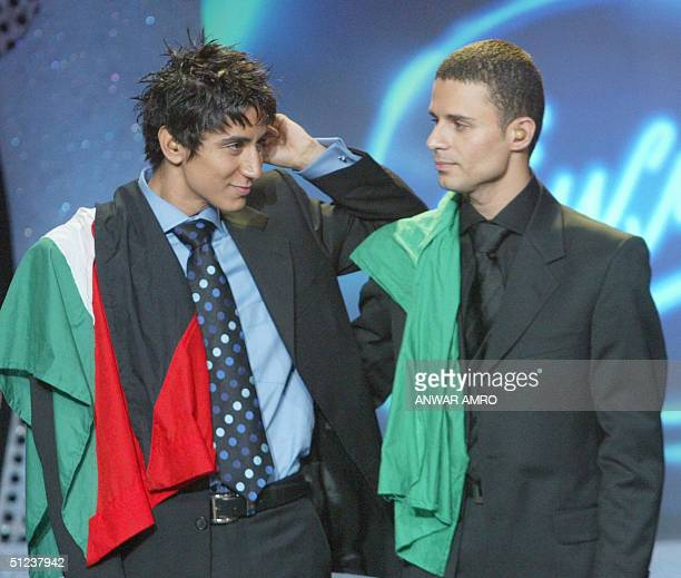 Finalists Libyan Ayman alAatar with a Palestinian flag and Palestinian Ammar Hassan with a Libyan flag stand on stage as they wait for the results of...