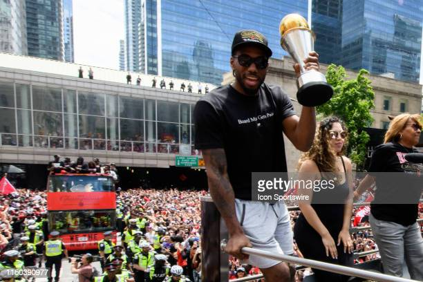 Finals MVP Kawhi Leonard raises the trophy on top of the bus during the Toronto Raptors Championship parade on June 13, 2019 in Toronto, ON, Canada.