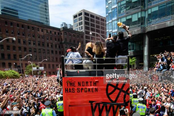 Finals MVP Kawhi Leonard raises the trophy on top of the bus during the Toronto Raptors Championship parade on June 13 2019 in Toronto ON Canada