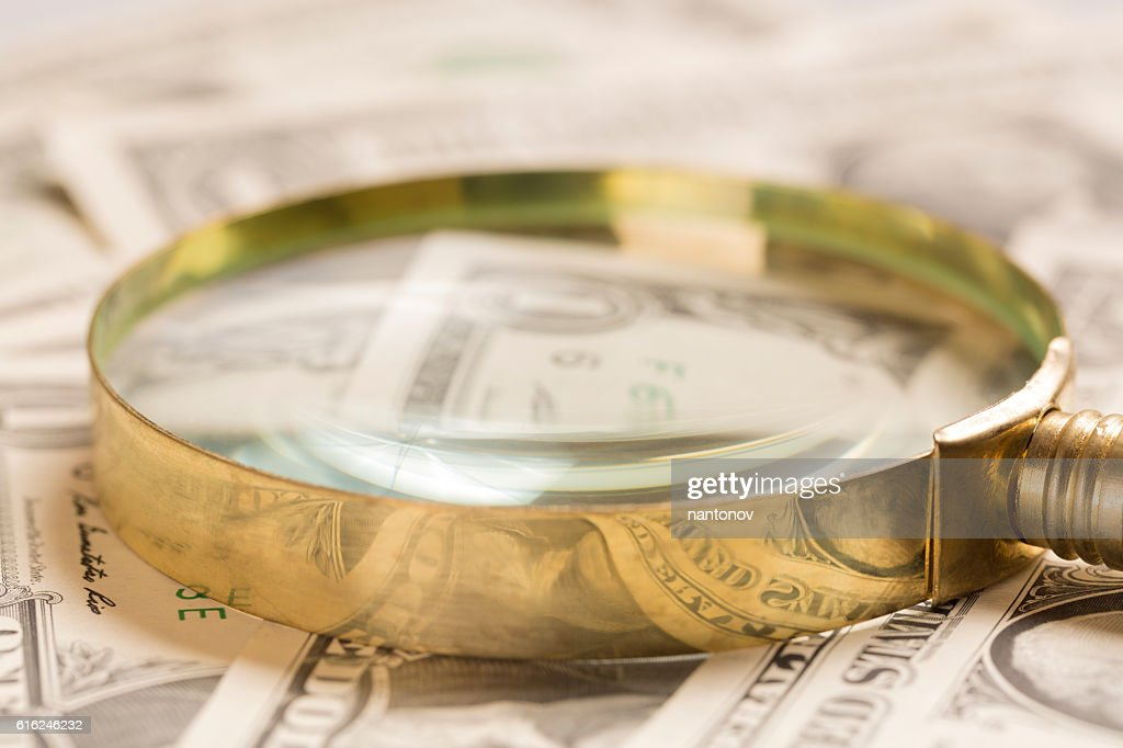 Finance concept. Gold magnifying glass on dollar banknotes : Stock Photo