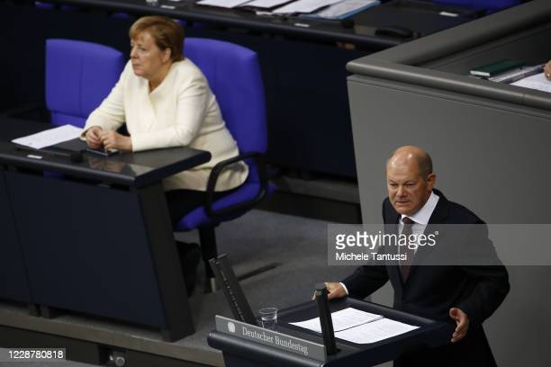Finance Minister and vice Chancellor Olaf Scholz speaks as German Chancellor Angela Merkel listens at the plenary room of the germans lower house of...