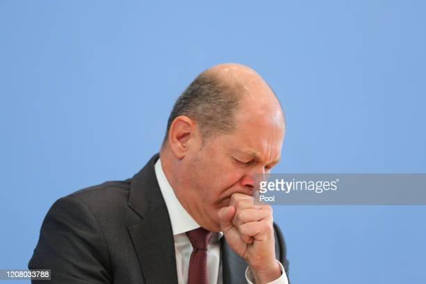 Finance Minister Olaf Scholz coughs as he speaks to the media about the German government's proposed new federal budget on March 23, 2020 in Berlin,...