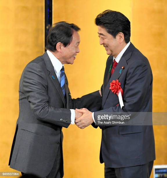 FInance Minister Taro Aso and Prime Minister Shinzo Abe shake hands during his faction's political fundraising party on April 12 2018 in Tokyo Japan