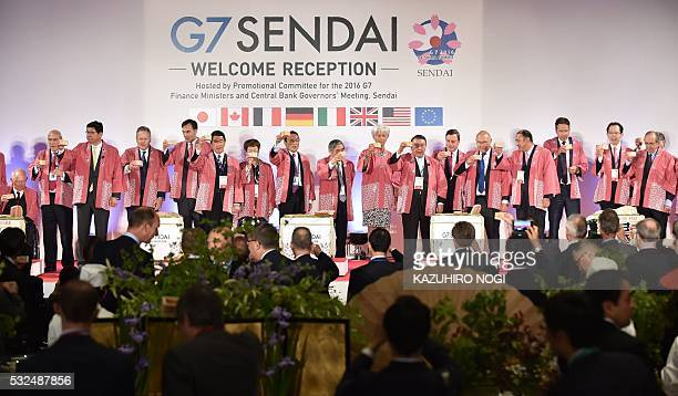 Finance ministers and central bankers from the G7 grouping make a ceremonial toast with sake after opening sake barrels at a welcome reception hosted...