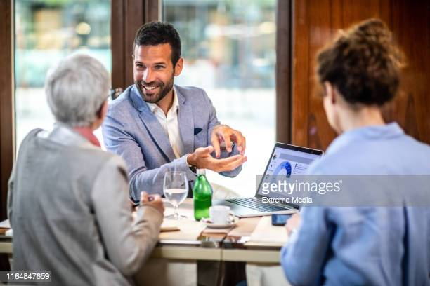 financial adviser explaining business strategy to two female business partners in a restaurant - risk stock pictures, royalty-free photos & images