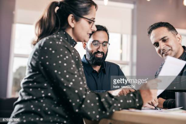 financial advisor and a couple - explaining stock pictures, royalty-free photos & images