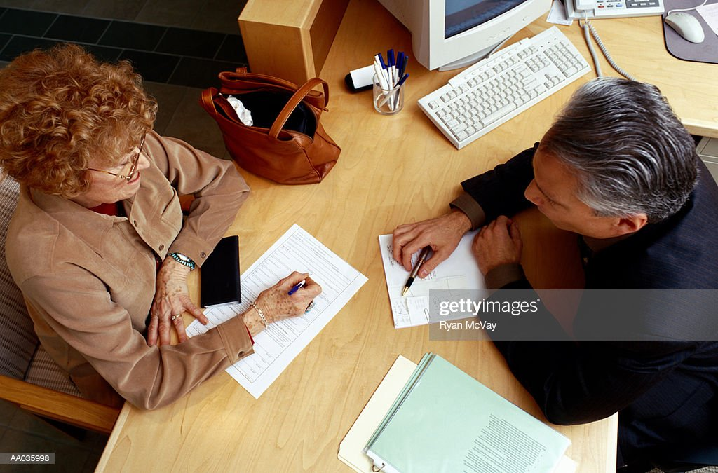 Financial Advisor Assisting Woman with Paperwork : Stock Photo