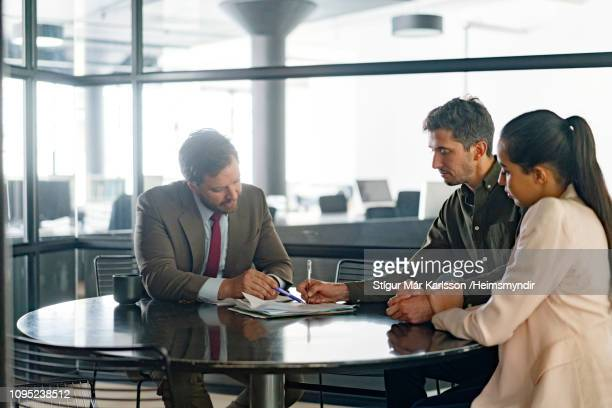 financial advisor explaining agreement to couple - bankieren stock pictures, royalty-free photos & images