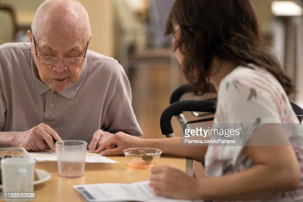 Financial Advisor Explaining Highlighted Part of Contract to Senior Client