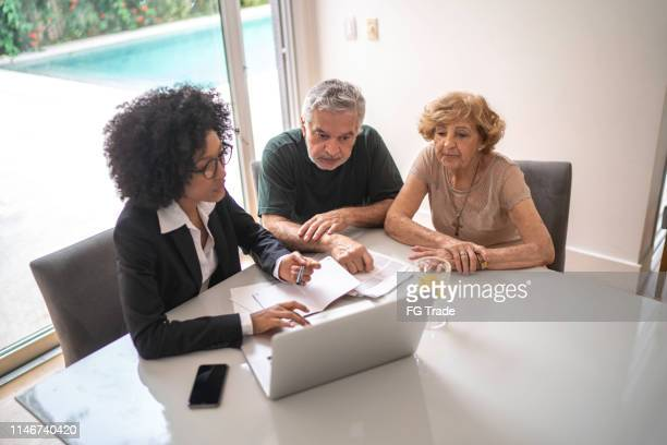 financial advisor helping a senior couple at home - life insurance stock pictures, royalty-free photos & images
