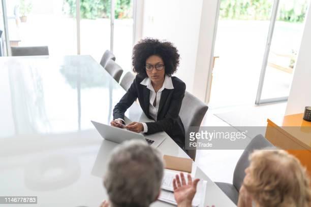 conselheiro financeiro que ajuda um par sênior em casa - agência imobiliária - fotografias e filmes do acervo