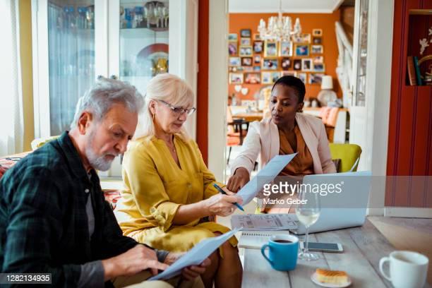 financial advisor helping a senior couple - fondo pensionistico personale foto e immagini stock