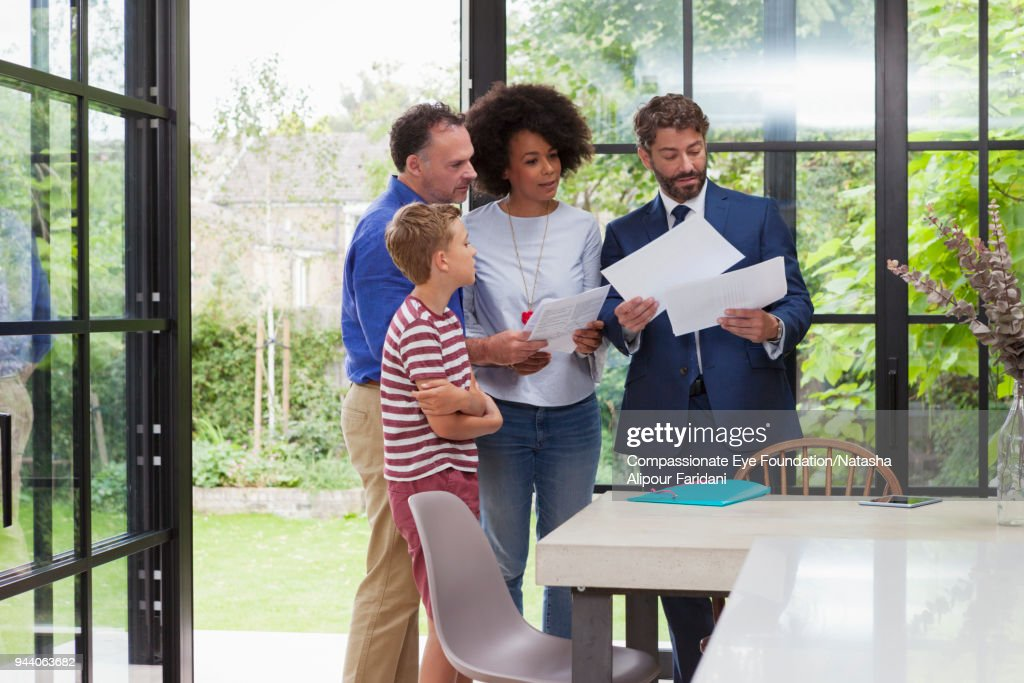 Financial advisor meeting with family in kitchen : Stock Photo