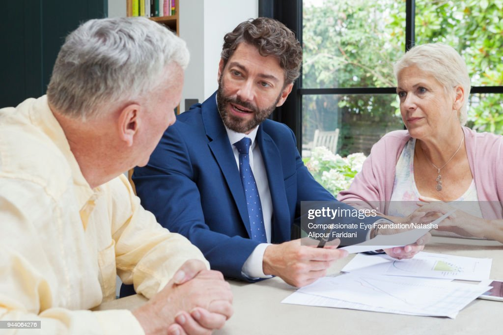 Financial advisor meeting with senior couple in kitchen : Stock Photo