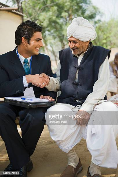 Financial advisor shaking hands with a farmer, Hasanpur, Haryana, India