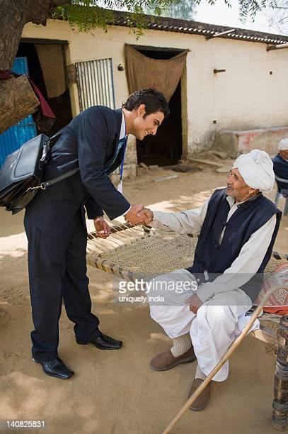 Financial advisor shaking hands with a farmer, Hasanpur, Haryana, India