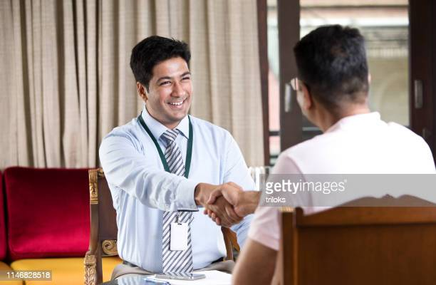 financial advisor shaking hands with customer - indian ethnicity stock pictures, royalty-free photos & images