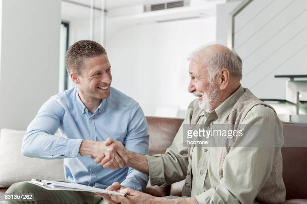 Finanzberater Händeschütteln mit älteren Mann