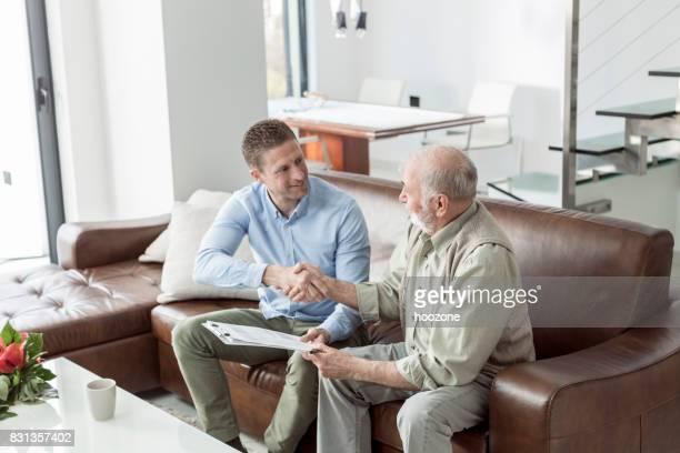 Financial advisor shaking hands with senior man