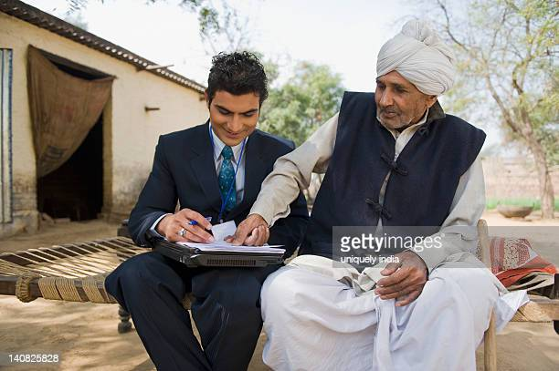 Financial advisor taking thumb impression of a farmer on a document, Hasanpur, Haryana, India