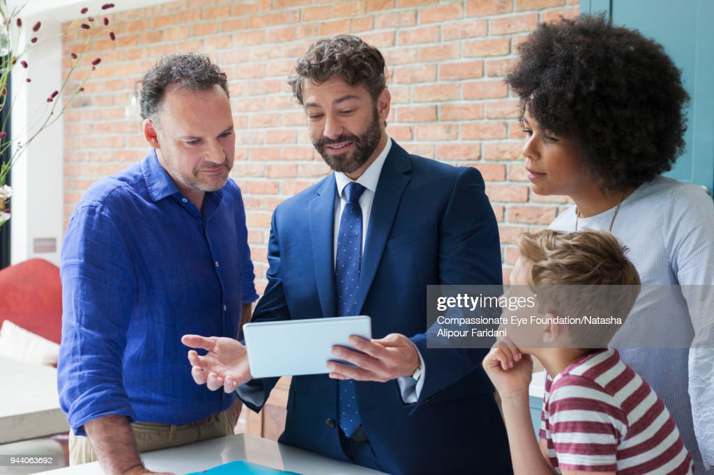 Financial advisor with digital tablet meeting with family in kitchen : Stock Photo