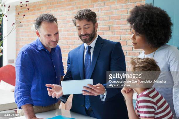 financial advisor with digital tablet meeting with family in kitchen - deal england stock photos and pictures