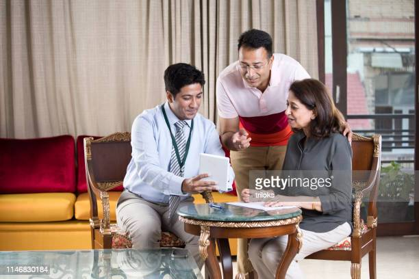 financial advisor with indian family - finance and economy stock pictures, royalty-free photos & images