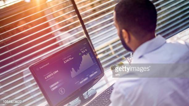 financial analyst using computer to study graphs in his office - financial technology stock photos and pictures