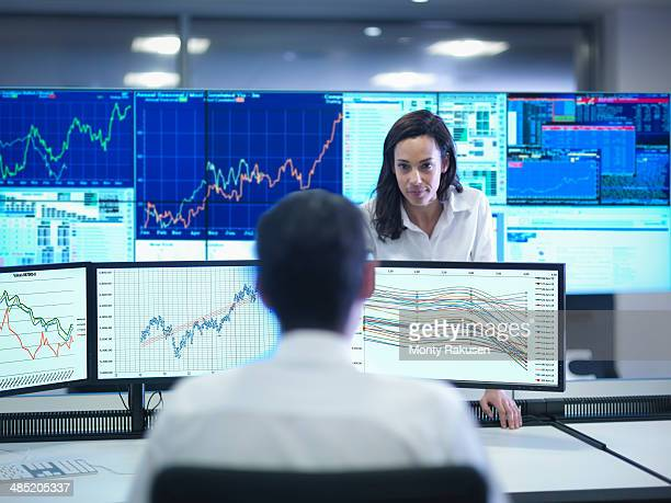 financial analysts looking at screens in control room - financial analyst stock photos and pictures
