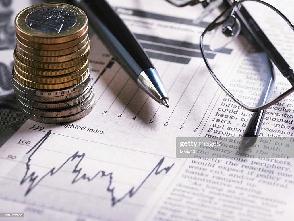 A financial chart with coins, glasses and pen : Stock Photo
