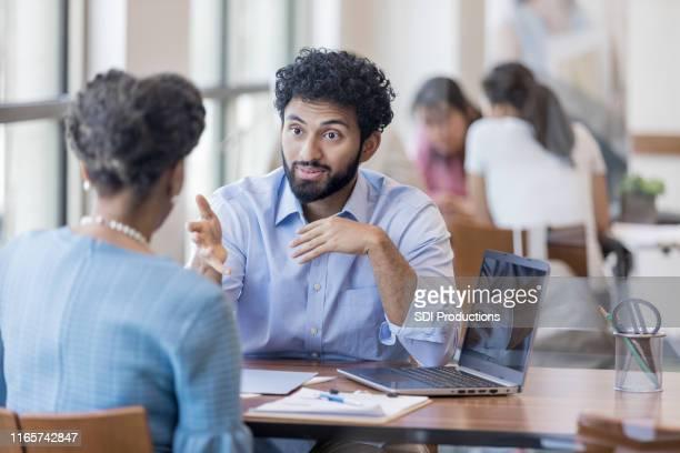 gestos del consejero financiero mientras responde las preguntas del cliente - representar fotografías e imágenes de stock