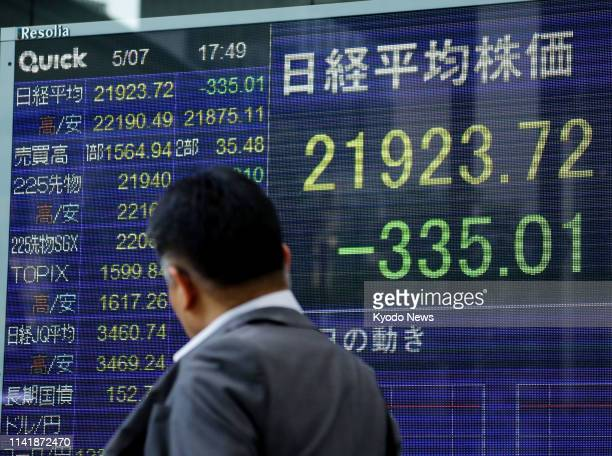 A financial data screen on a Tokyo street shows the Nikkei Stock Average closing down more than 300 points on May 7 the first trading day after...