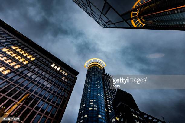 financial downtown district at dusk against storm clouds in frankfurt, germany - ominous stock photos and pictures