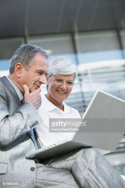 financial planner and client looking at a laptop - hand on chin stock pictures, royalty-free photos & images