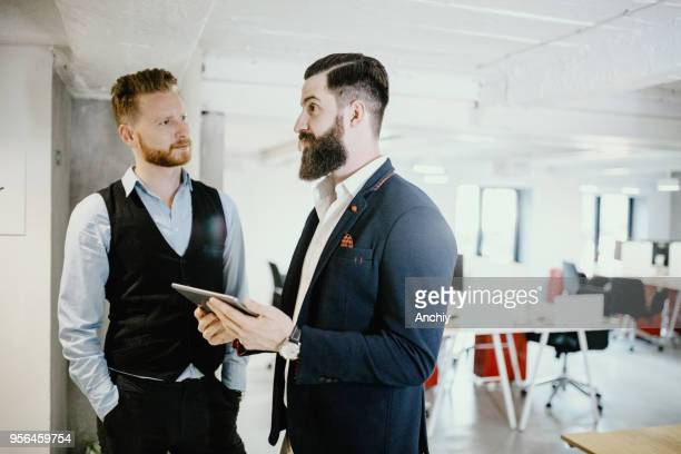 financial planner talking to his coworker - ginger banks stock pictures, royalty-free photos & images