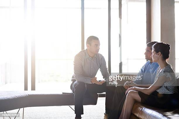 financial planner talking with couple in office - financial advisor stock pictures, royalty-free photos & images