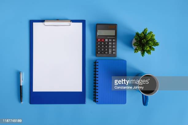 financial planning. clipboard and calculator on blue desk. - knolling concept stock pictures, royalty-free photos & images