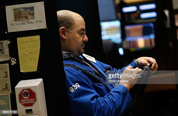 A financial professional works in a cubbyhole on the floor of the New York Stock Exchange near the end of the trading day May 14 2010 in New York New...