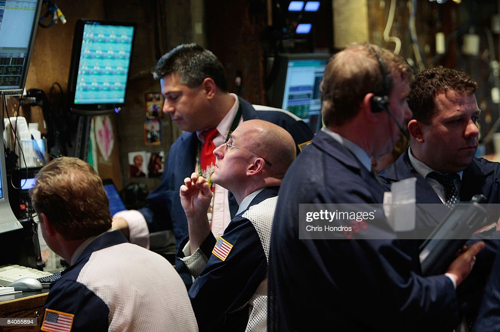 Financial professionals on the floor of the New York Stock Exchange work after hearing news of the Federal Reserve's rate cut December 16, 2008 in New York City. The Federal Reserve slashed the federal funds rate, the interest banks charge each other, to a record low of zero to one quarter percent, sending stocks higher in mid-afternoon trading.