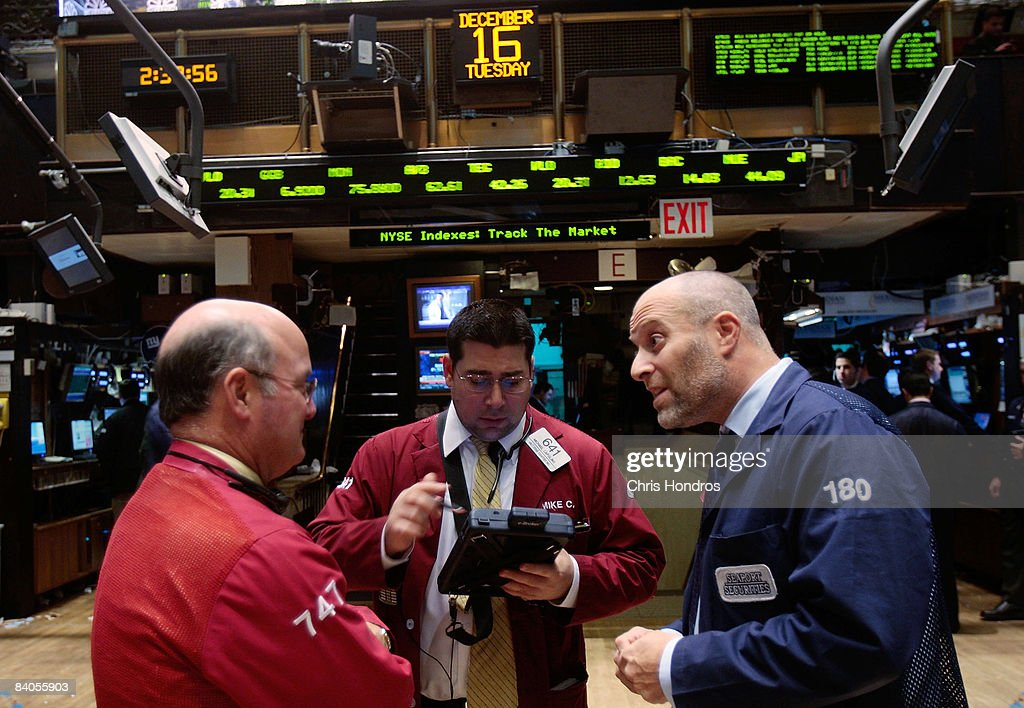 Financial professionals talk on the floor of the New York Stock Exchange after the Federal Reserve's rate cut December 16, 2008 in New York City. The Federal Reserve slashed the federal funds rate, the interest banks charge each other, to a record low of zero to one quarter percent, sending stocks higher in mid-afternoon trading.
