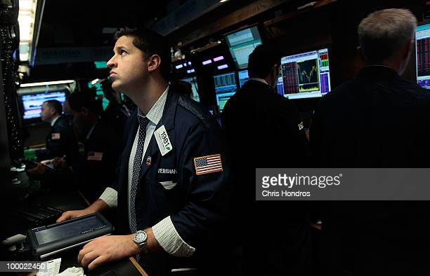 Financial professionals work in a cubbyhole on the floor of the New York Stock Exchange near the end of the trading day May 20 2010 in New York City...