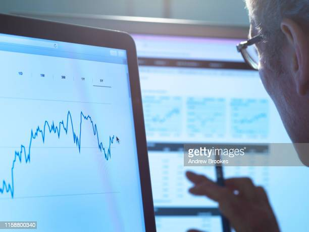 financial services, stock analyst researching share price data of a company on the computer - analysing stock pictures, royalty-free photos & images