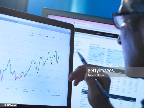 financial services, stock analyst researching share price data of a company on the computer - business strategy stock pictures, royalty-free photos & images