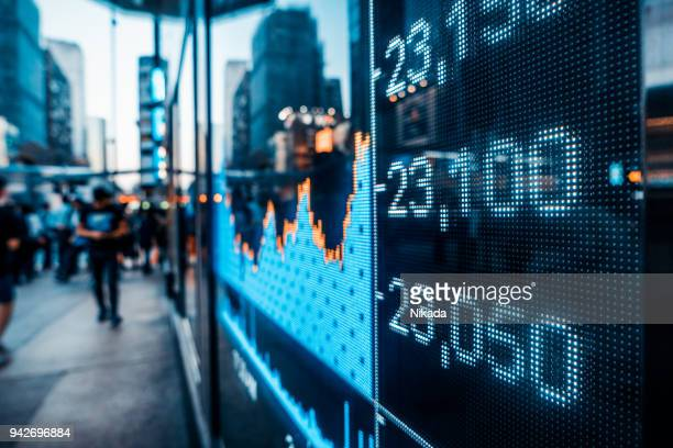 financial stock market numbers and city light reflection - finanza foto e immagini stock