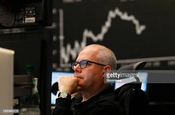 A financial trader monitors data on his computer screens beneath a display of the DAX Index curve at the Frankfurt Stock Exchange in Frankfurt...