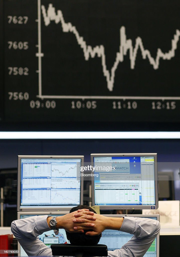 A financial trader monitors data on his computer screens beneath the DAX index curve inside the Frankfurt Stock Exchange in Frankfurt, Germany, on Tuesday, Feb. 27, 2013. Stocks rose, the euro strengthened from a seven-week low and Italian 10-year bonds gained after the country sold 6.5 billion euros ($8.5 billion) of debt amid political turmoil. Photographer: Ralph Orlowski/Bloomberg via Getty Images