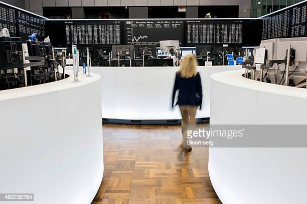 A financial trader passes between banks of computer monitors on the trading floor as the DAX Index curve is displayed beyond at the Frankfurt Stock...
