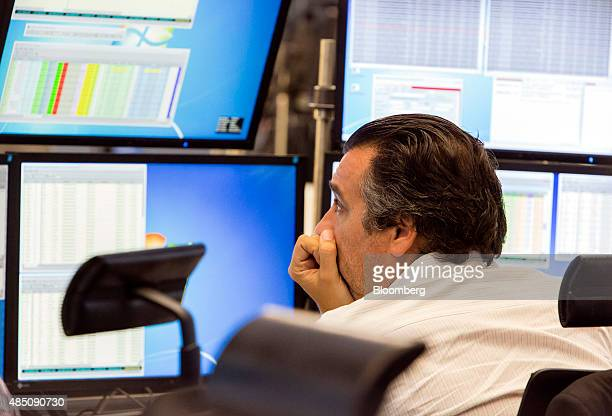 A financial trader reacts as he monitors data on computer screens at the Frankfurt Stock Exchange in Frankfurt Germany on Monday Aug 24 2015...
