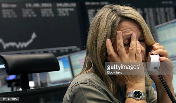 A financial trader reacts as she speaks on the telephone in front of a display of the DAX Index curve at the Frankfurt Stock Exchange in Frankfurt...